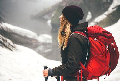 Girl wearing a backpack in the snowy outdoors